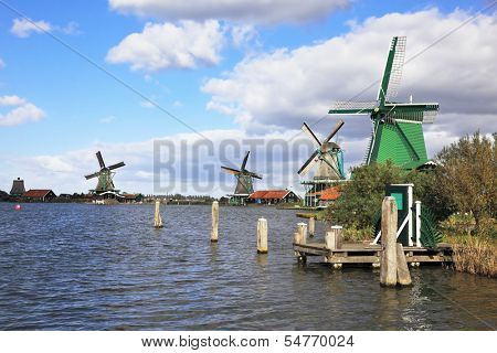 The village - an ethnographic museum in Holland. Four windmills and berthing columns on the bank of the channel