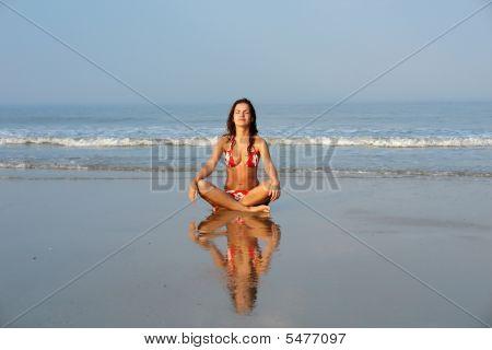 Beautiful girl doing yoga on the ocean beach