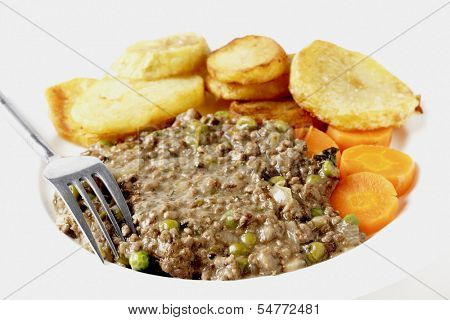 High key shot of minced beef cooked with onion, garlic, peas and herbs, served with saute potatoes and boiled carrots. This is a simple, slightly old-fashioned British-style meal,