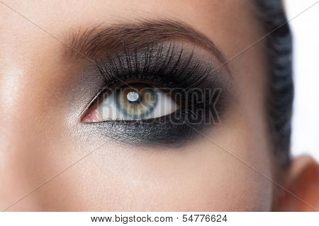 Closeup of beautiful woman eye with bright stylish makeup with long lashes
