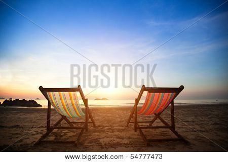Pair of beach loungers on the deserted coast sea at sunrise, perfect vacation concept.