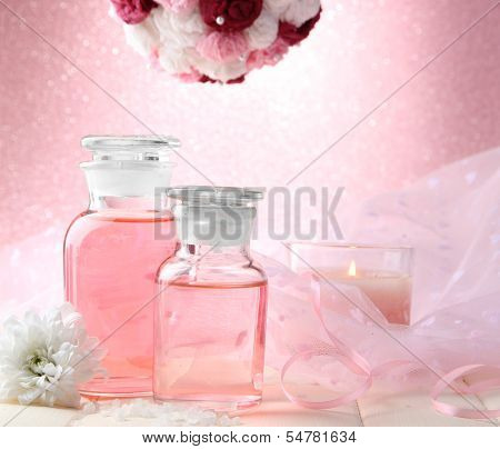 Glass bottles with color essence, on pink background