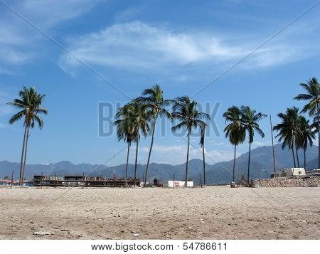 Beach With Coconut Tree, Constuction Of Buildings And Mountains In The Background