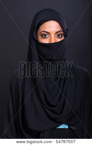 portrait of young muslim woman on black