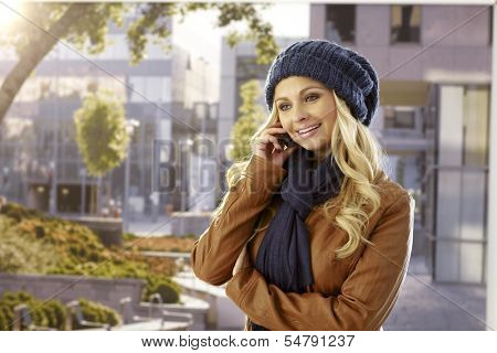 Pretty young woman talking on mobilephone outdoors at autumn.