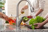 stock photo of sink  - Segregation of duties during making together the salad in family