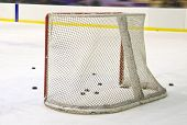 stock photo of bandy stick  - ice hockey net with puck on ice - JPG