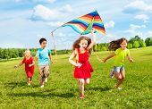 stock photo of kites  - Group of four kids running in the park with kite happy and smiling on summer sunny day - JPG