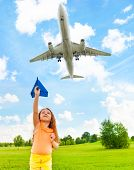 picture of 6 year old  - Happy 6 years old girl holding blue paper airplane with jet flying over in the sky - JPG