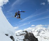 foto of snowboarding  - Jumping snowboarder keeps one hand on the snowboard on blue sky background - JPG