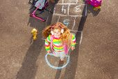 foto of hopscotch  - Nice little girl with blond curly hair jumping over hopscotch game after school with bags and scooter laying near - JPG