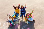 picture of hopscotch  - Group of four boys and girls friends in autumn clothes painting with chalk on the asphalt lifting hands with smile on theirs faces - JPG