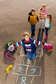 stock photo of hopscotch  - Boy jumping on hopscotch game with friends boys an girls standing by with school bags laying near - JPG
