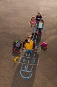 stock photo of hopscotch  - Boy jumping on hopscotch game with mates boys an girls standing by with school bags laying near - JPG