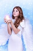 image of blue angels  - Cute Christmas angel on blue snowy background - JPG