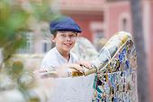 foto of gaudi barcelona  - Cute little boy on a colorful ceramic bench at Parc Guell designed by Antoni Gaudi - JPG