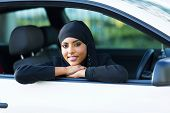 beautiful young muslim woman sitting in her new car