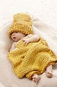 stock photo of knitwear  - Adorable newborn baby lying in knitwear - JPG