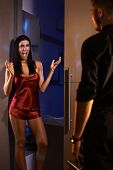 stock photo of nightie  - Sexy woman shouting happy when man arriving from work - JPG