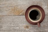 Coffee cup on wooden table texture. View from above