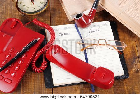 Telephone and notepad and other items, on wooden background
