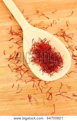 stigmas of saffron in wooden spoon on wooden background close-up
