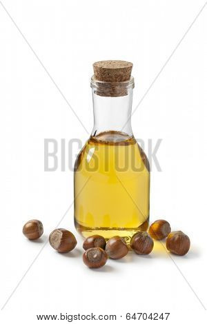 Hazelnut oil and hazelnuts on white background