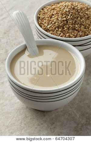 Bowls with tahini paste and roasted sesame seeds
