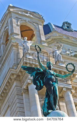 Statue of an angel with laurel wreath in front of Art museum on  Maria Theresa square in Vienna