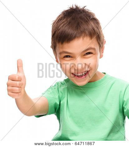 Cute little boy is showing thumb up sign, isolated over white