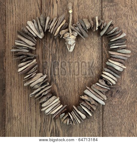 Driftwood love heart with small wooden pieces over old oak background.