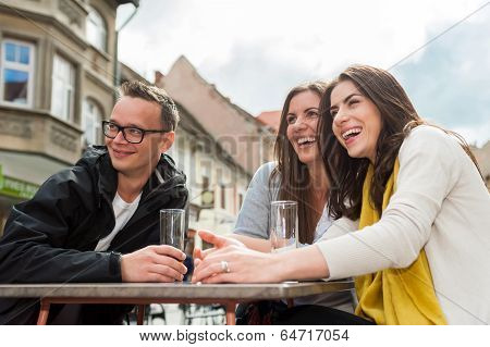Three friend socializing at restaurant table