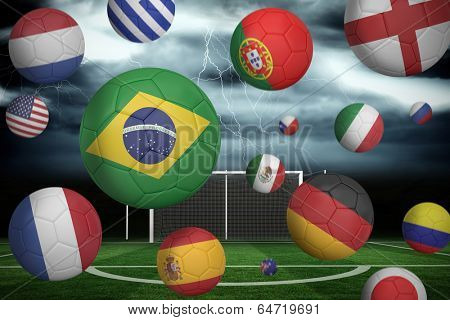 Footballs in various flag colours against football pitch under stormy sky