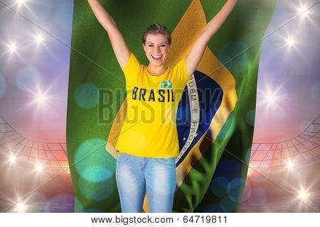 Excited football fan in brasil tshirt holding brasil flag against large football stadium under purple sky