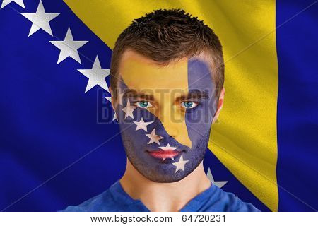 Composite image of serious young football fan in face paint against digitally generated bosnian flag