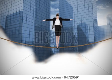 Businesswoman performing a balancing act against view of dull cityscape