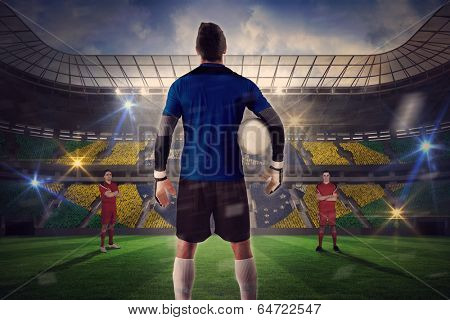 Composite image of goalie facing opposition against large football stadium with brasilian fans