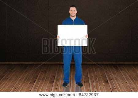 Handsome mechanic showing card against dark room with floorboards
