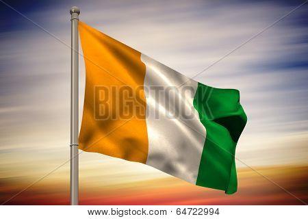 Ivory coast national flag on flagpole against blue and orange sky