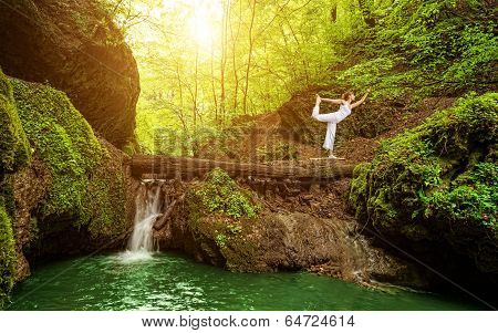 Woman practices yoga in nature the waterfall.