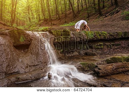 Woman practices yoga in nature the waterfall. forest; Urdhva phanurasana; Dhanurasana pose