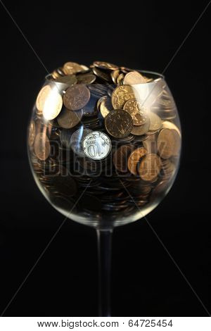 Coins lay in a wine glass on a black background