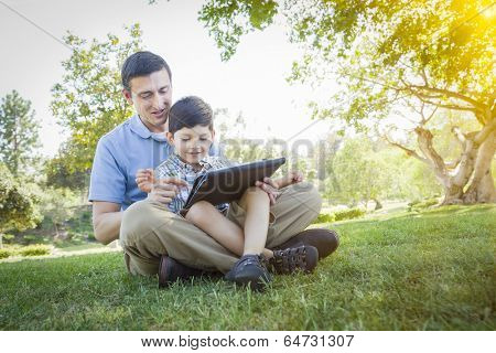 Handsome Mixed Race Father and Son Playing on a Computer Tablet Outside.