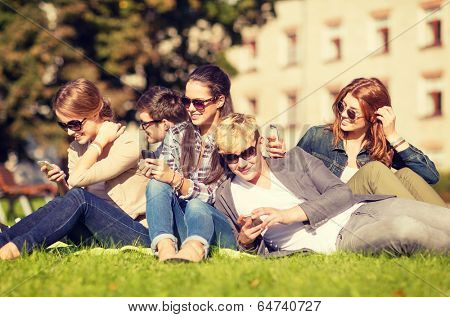education, technology, internet, summer holidays, social networking and teenage concept - group of teenagers with smartphones