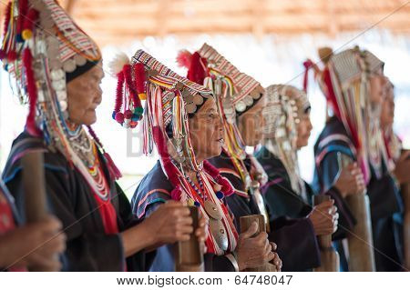 CHIANG RAI, THAILAND - DEC 4, 2013: Unidentified Akha hill tribe indigenous people of Thailand in traditional clothes and folk costumes. Tourist travel tours to cultural villages are very popular