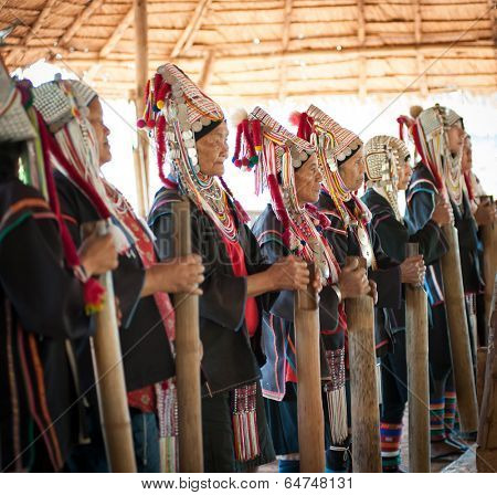 CHIANG RAI, THAILAND - DEC 4, 2013:Unidentified Akha hill tribe indigenous people dance in traditional clothes. Tourist travel tours to cultural villages are very popular. Folk costumes and jewelry