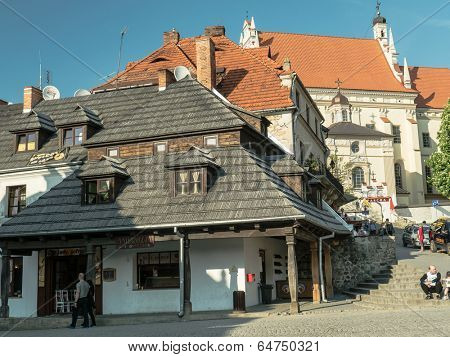 KAZIMIERZ DOLNY, POLAND - MAY 01 2014: Kazimierz Dolny town square surrounded by picturesque medieval houses and Parish Church Fara on the hill