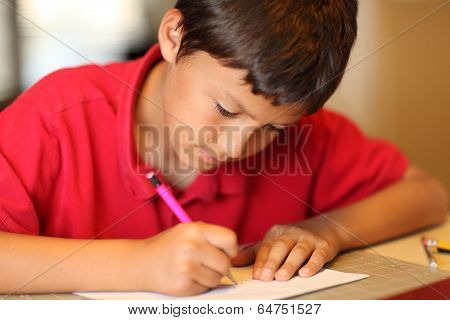 Young boy drawing for homework