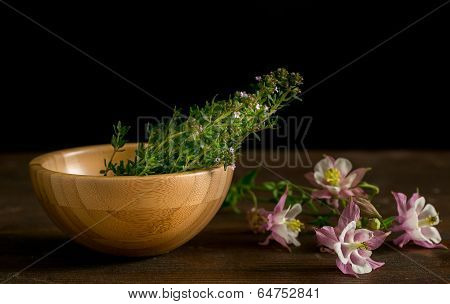 Wooden bowl with thyme and pink flowers