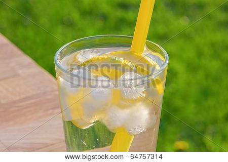 Simple glass of ice water with lemon slices and straw on a table. Taken outdoors with a out of focus